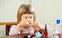 Three year old girl making manicure Stock Photos