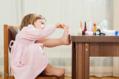 Three year old girl making pedicure royalty free stock photos