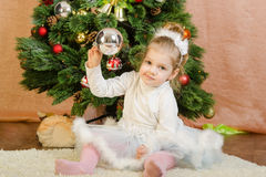 Three year old girl playing Christmas balls Royalty Free Stock Photo