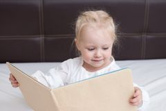Three year old girl reading a book stock images