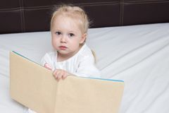 Three year old girl reading a book royalty free stock image