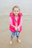 Three year old girl standing on the beach with shells in hand Stock Images
