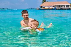 Toddler boy learns to swim with father royalty free stock photos