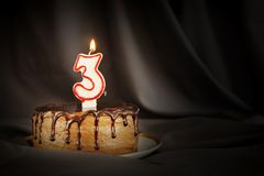 Three years anniversary. Birthday chocolate cake with white burning candle in the form of number Three. Dark background with black cloth stock photo