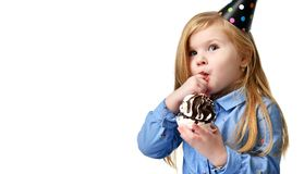 Three years girl kid eat sweet chocolate cake celebrating in birthday cap  Stock Image
