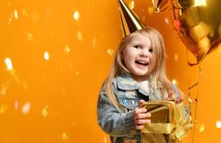 Three years girl toddler kid with gold presents balloons and birthday cap celebrating. On yellow background Stock Images