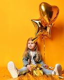 Three years girl toddler kid with gold presents balloons and birthday cap celebrating. On yellow background Stock Photo