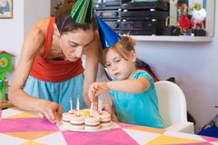 Child and mother putting candles on party cake. Three years old blonde child and women with colored cone caps, at birthday party, putting candles in flower royalty free stock image