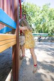 Little girl climbing in playground and mother watching Stock Photo