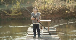 Three years old boy catching fish with a big fishing rod on sunny day he standing on the bridge. slow motions. stock footage