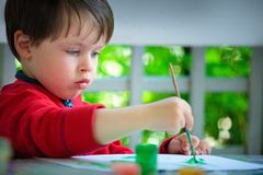 Three years old boy painting with brush Royalty Free Stock Photo
