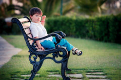 Three years old boy sitting on bench in park Stock Photography