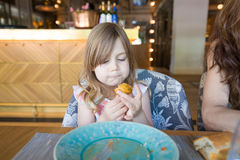 Little girl eating croquette with hand in restaurant Royalty Free Stock Photos