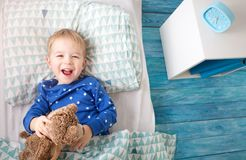 Three years old child lying in bed Stock Image