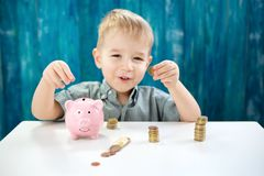 Three years old child sitting st the table with money and a piggybank. Happy boy with euro coins royalty free stock images