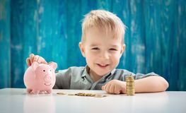 Three years old child sitting st the table with money and a piggybank. Happy boy with euro coins royalty free stock photography