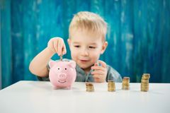 Three years old child sitting st the table with money and a piggybank Royalty Free Stock Images