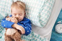 Three years old child sleeping in bed with alarm clock Stock Image