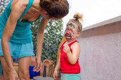 Little child with painted face screaming next to mother Stock Photos