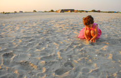 Three years old girl playing with sand on the beach Stock Image