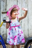 Three years old girl sending regards with a bicycle stock images