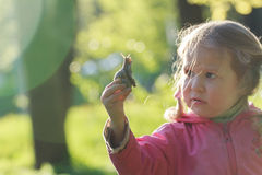 Three years old preschooler girl with short. Pigtails is holding edible snail stock image