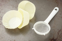 Three yellow baking cups and sifter Royalty Free Stock Photography