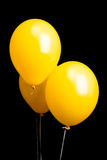 Three yellow balloons isolated on black Stock Images