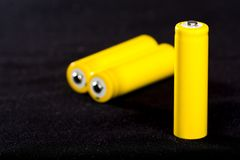 Three yellow batteries close-up on a dark black blurred background. Electrics. Battery power. Accumulator on the fabric with vill. I. Space for text royalty free stock photos