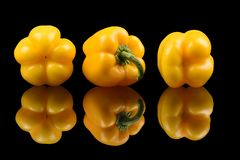 Three yellow Bell peppers on glass with bright and clear reflection stock photo