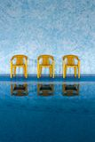 Three yellow chairs at swimming pool Stock Photo