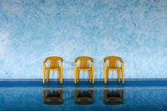 Three yellow chairs at swimming pool Royalty Free Stock Image