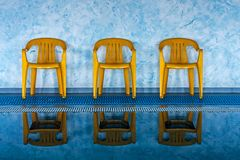 Three yellow chairs at swimming pool Royalty Free Stock Images