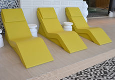 Three yellow chaise longue in the pool Stock Images