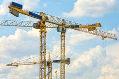 Three yellow cranes. On cloudy blue sky background stock photos