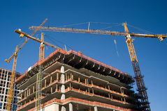 Three yellow cranes over construction site Stock Images