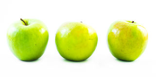 Three yellow and green apples lined up next to each other on a white background Royalty Free Stock Photos
