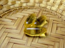 Three capsules of fish oil lie on a wicker straw plate royalty free stock photo