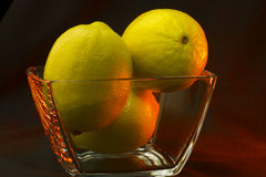 Three lemons on transparent vase Royalty Free Stock Images
