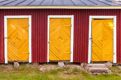 Three yellow locked doors in red rural barn. Wall, flat background photo texture Royalty Free Stock Images