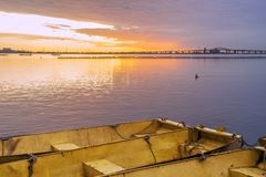 Three yellow metal boats tied together on calm lake at dawn unde Stock Image
