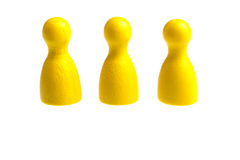 Three yellow pawn game figures Stock Photo