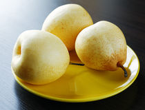 Three yellow pears on the plate Stock Images