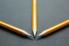 Three yellow pencils on black paper royalty free stock photo