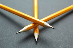 Three yellow pencils on black paper royalty free stock photography