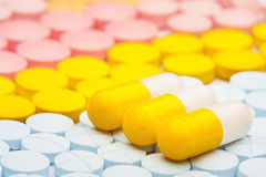 Three yellow pills on background of colored medical pills. Three yellow pills on a background of colored medical pills Stock Image