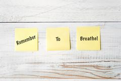Three Yellow Post It notes with Message Remember to Breathe!. Against weathered white wood background Royalty Free Stock Photo