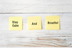 Three Yellow Post It notes with Message Stay Calm and Breathe!. Against weathered white wood background Stock Image