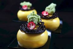 Three yellow round desserts with chocolate nest decoration, cranberries and pistachio sponge stock photos