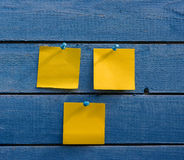 Three yellow stickers on old  wooden wall Royalty Free Stock Photography